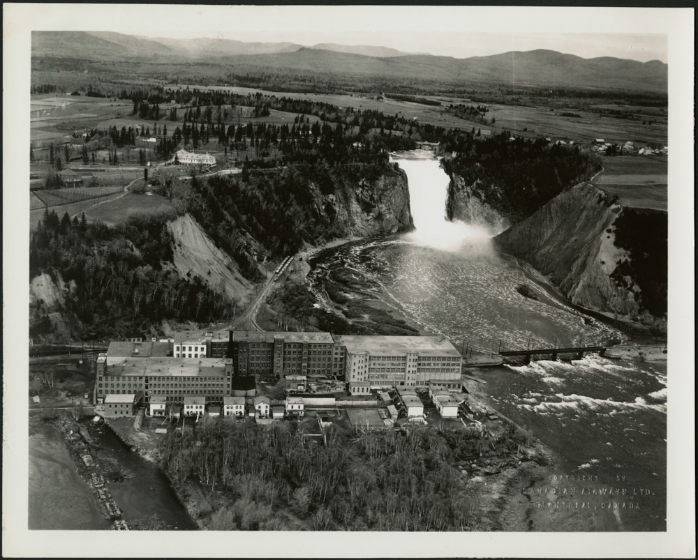 A black-and-white aerial photograph showing a factory beside a river, with a large waterfall in the background.