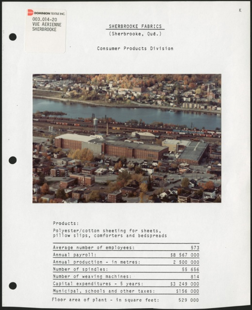 A page from a binder featuring a colour aerial photograph of a factory in a town, near a river, with statistics printed below the photograph.