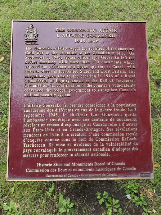 A red plaque with gold writing featuring the Arms of Canada in the top left corner.