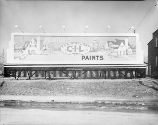 "Black-and-white photograph showing a large rectangular billboard anchored to an embankment and featuring an advertisement for CIL. The ad looks like a painting, with a house at each end, in a suburban landscape. Between the two houses, the oval CIL logo is visible, with the words ""Peintures"" in the top left and ""Paints"" in the bottom right."