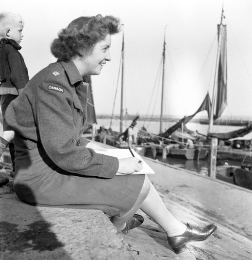 Black-and-white photograph taken from the side showing a smiling woman in uniform sitting on a pier with a drawing tablet and pencil in hand. In the background, a young blond child is standing, and sailboats are docked nearby