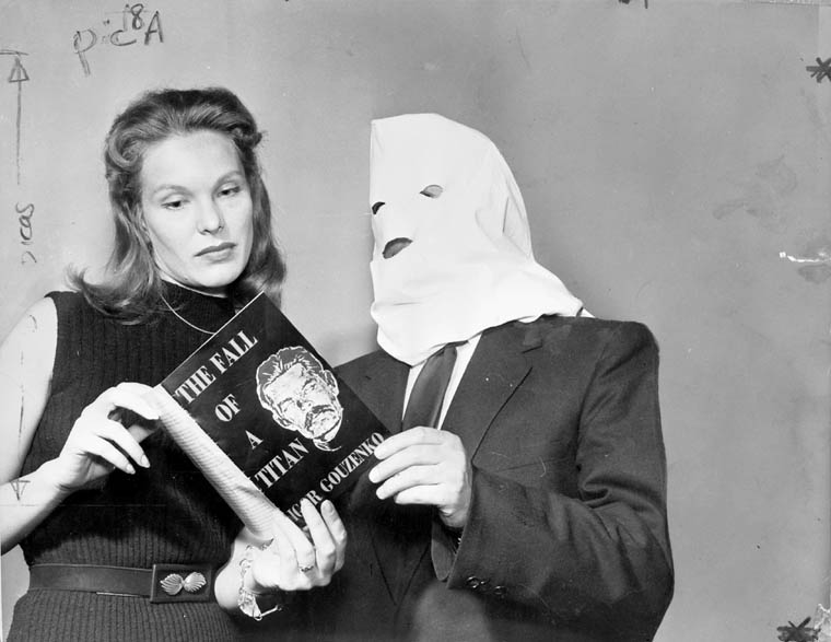 A black-and-white photograph of a woman and a man with a hood covering his face, looking at a book entitled The Fall of a Titan bearing an image of Joseph Stalin along with the name of the author, Igor Gouzenko, on the cover.