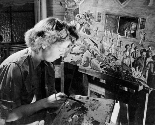 A black-and-white photograph, taken from the side, of a woman painting at an easel, holding a paintbrush and palette