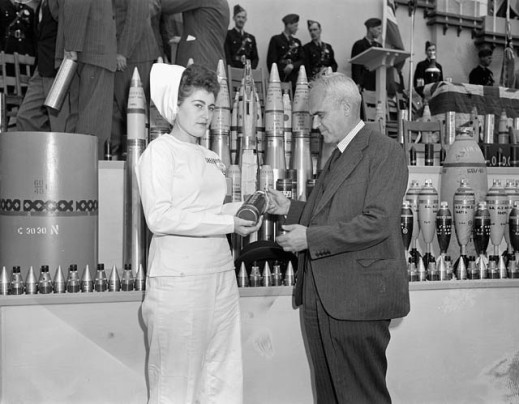Black-and-white photograph of a female employee wearing a white uniform and cap, holding a projectile for presentation to the Honourable C.D. Howe. Behind them, several projectiles of different sizes are displayed on a table. In the background, a few civilians and military personnel are standing on a platform behind a lectern.