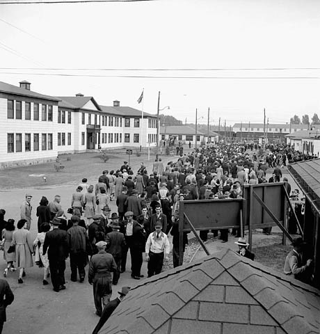 Black-and-white photograph showing employees in front of factory buildings, moving away from what appears to be a locker building. Most are seen from behind; others are facing the camera or talking to each other. In the background are a few train carriages.