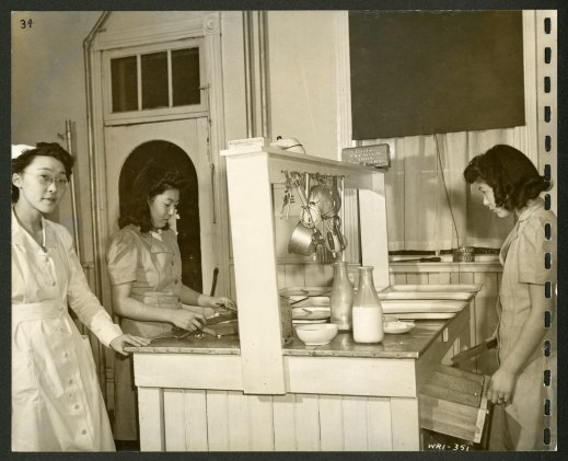 Three women, one of whom is a nurse, are standing around a kitchen island on which there are trays, dishes and bottles of milk. Utensils are hanging from the rack that runs down the middle of the unit.