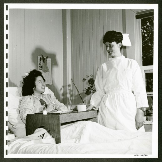 From left to right: Hospitalized woman (internee) in bed. Nurse standing on the right.