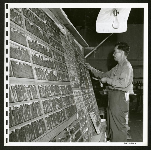 A man is standing in front of a large, tilted shelving unit filled with Japanese characters used in a printing press.