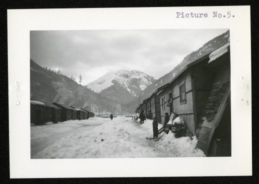"From right to left: Children in front of shiplap shacks with snow shovelled against walls. Internee in distance walking down makeshift ""street."" Tar paper, to protect the shacks from the elements, is visible on the shack walls."