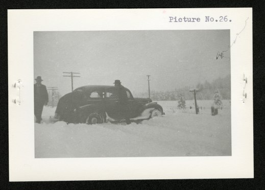 Three men and a car in a snowstorm: (from left to right) one man standing at the rear of the car, a second man bent over the back right tire, and a third man going towards the car to assist.