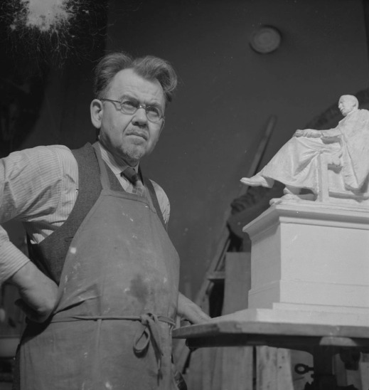 Black-and-white photo of a man wearing an apron, standing next to a model of a statue. He is wearing glasses and has his fist on his hip.