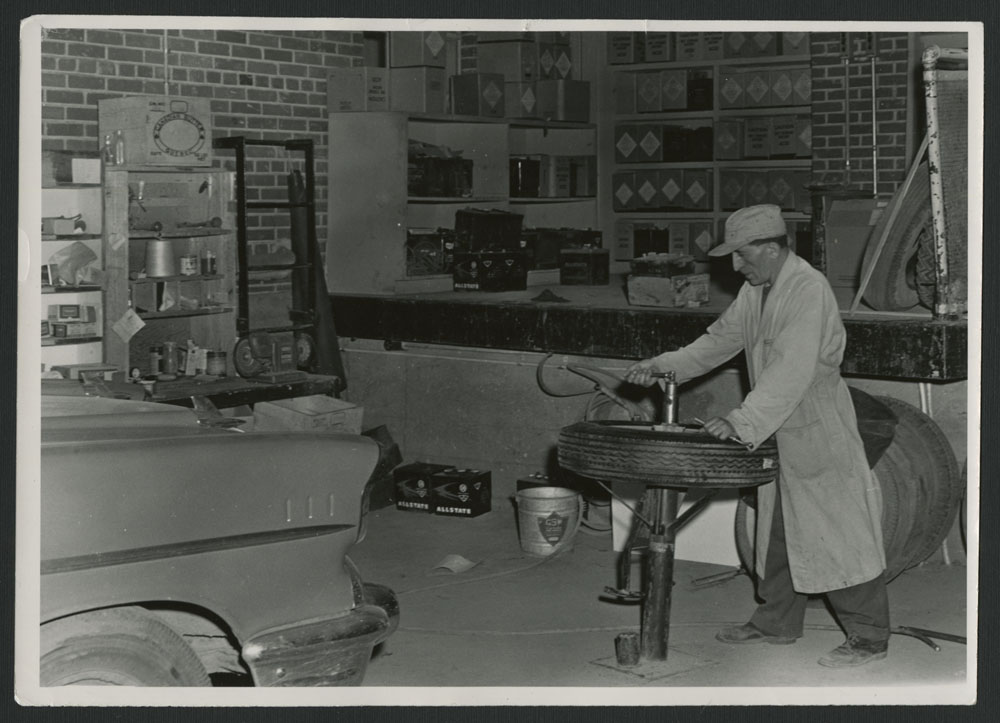 Black-and-white photograph of a mechanic wearing an overcoat and a cap who is working on a tire with a counter in the background and part of a car visible in the foreground.