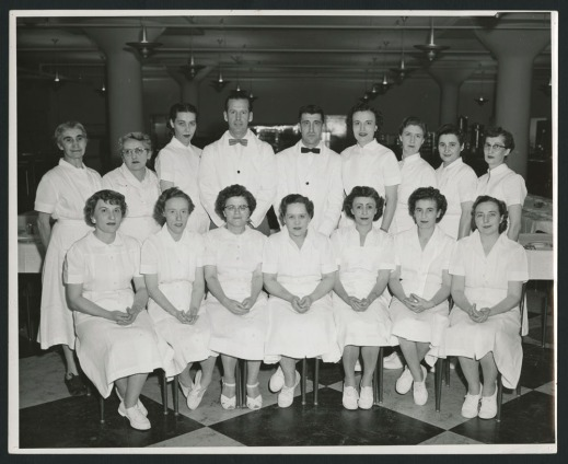 A formal posed group shot with seven women seated and seven women and two men standing, wearing white staff uniforms.