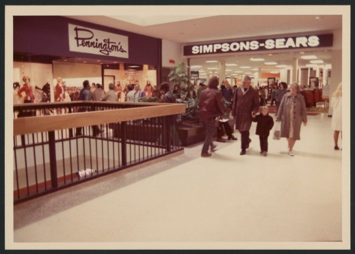 "The interior photograph shows shoppers on the upper floor of the mall with ""Pennington's"" and ""Simpsons-Sears"" signs in the background."