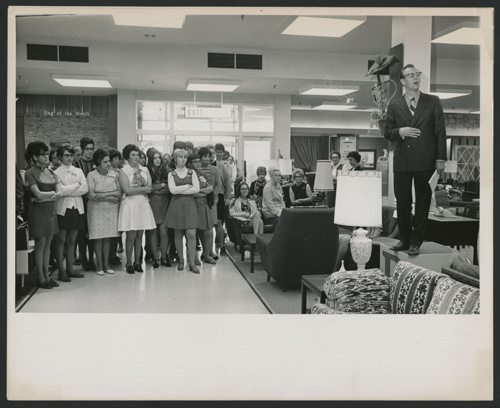 Black-and-white photograph of a man standing on a table speaking to a large group of women.