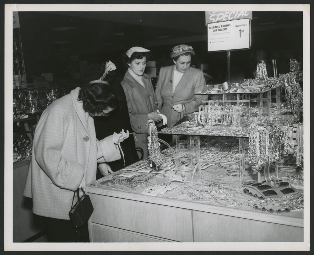 "Black-and-white photograph of four women closely examining the jewelry on a department store table, which has a sign that reads ""Special: Necklaces, Earrings and Broaches, $1.00."""