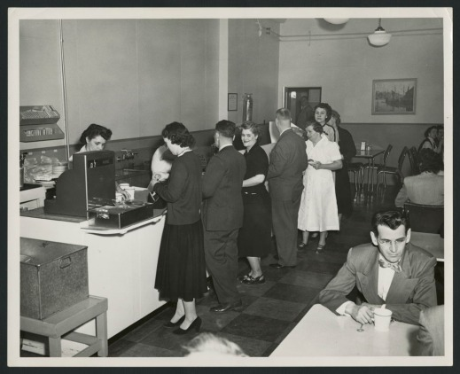 A black-and-white photographs showing the staff at department store cafeterias. It shows customers in line to purchase food items, a woman working at the cash register and a man at a table with a cup of coffee