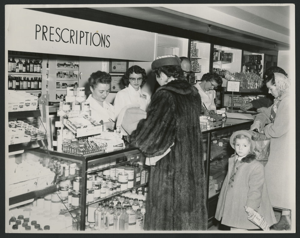 "Black-and-white photograph showing three women and a child at a counter, and three women working behind the counter, with ""Prescriptions"" on a sign above their heads."