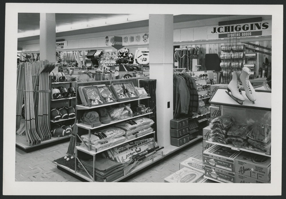 Black-and-white photograph showing the sports department of a department store, with hockey sticks, clothing, fishing rods and figure skates visible on the shelves.