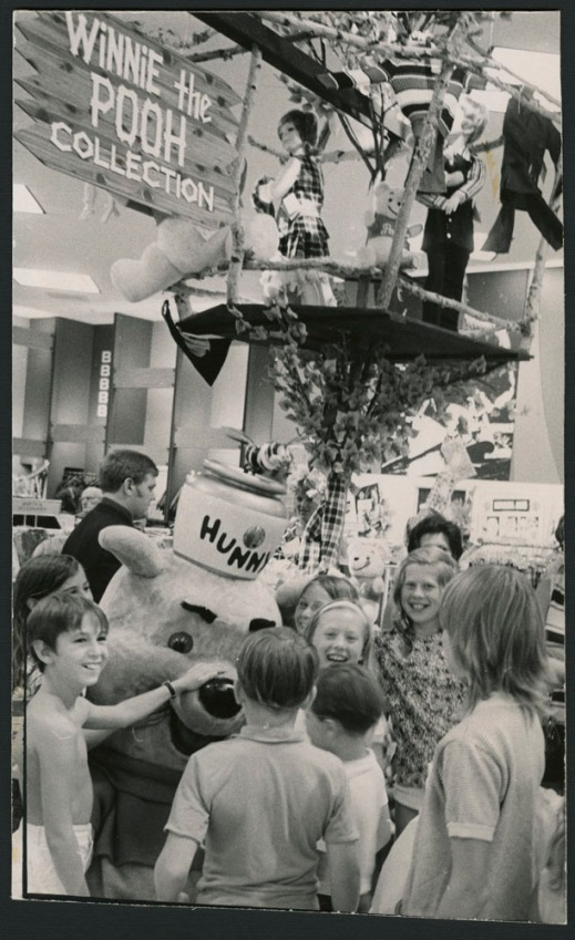 "Black and white photograph showing children gathered around a large Winnie-the-Pooh mascot, with a treehouse and a ""Winnie-the-Pooh Collection"" sign in the background."
