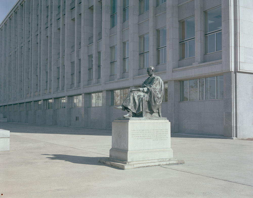 Colour photo of a statue of a seated man with a large building in the background.