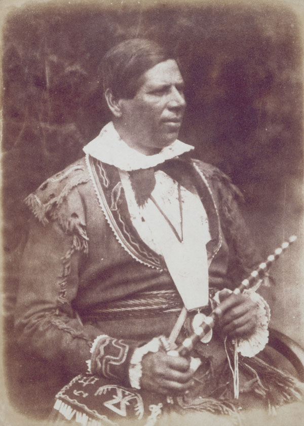 A sepia photograph of a seated man dressed in traditional quill design buckskin jacket and bag, holding a ceremonial pipe and a string of wampum beads.