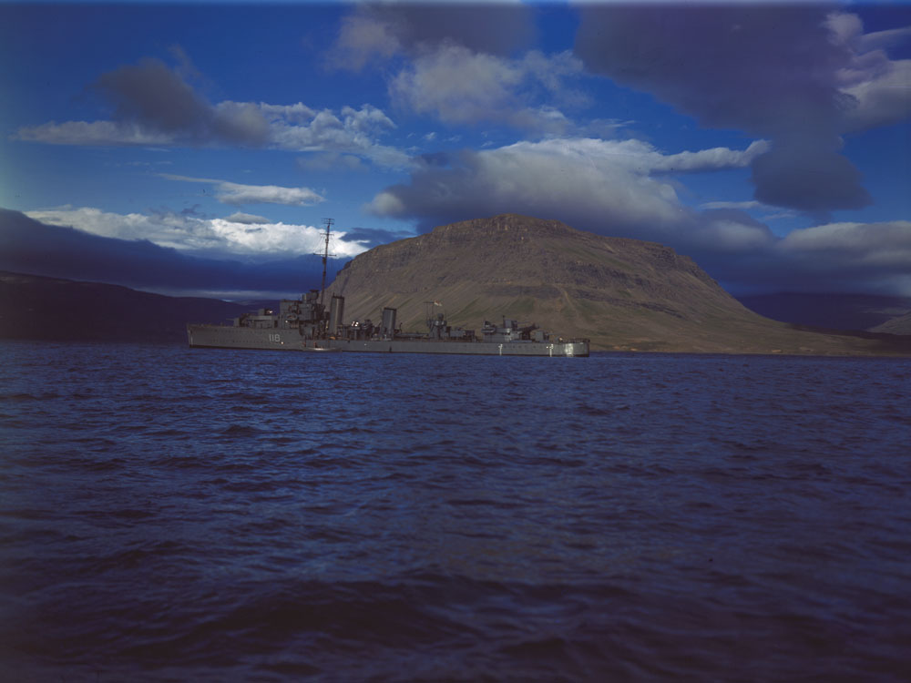 Colour photograph of a large ship in front of an island.