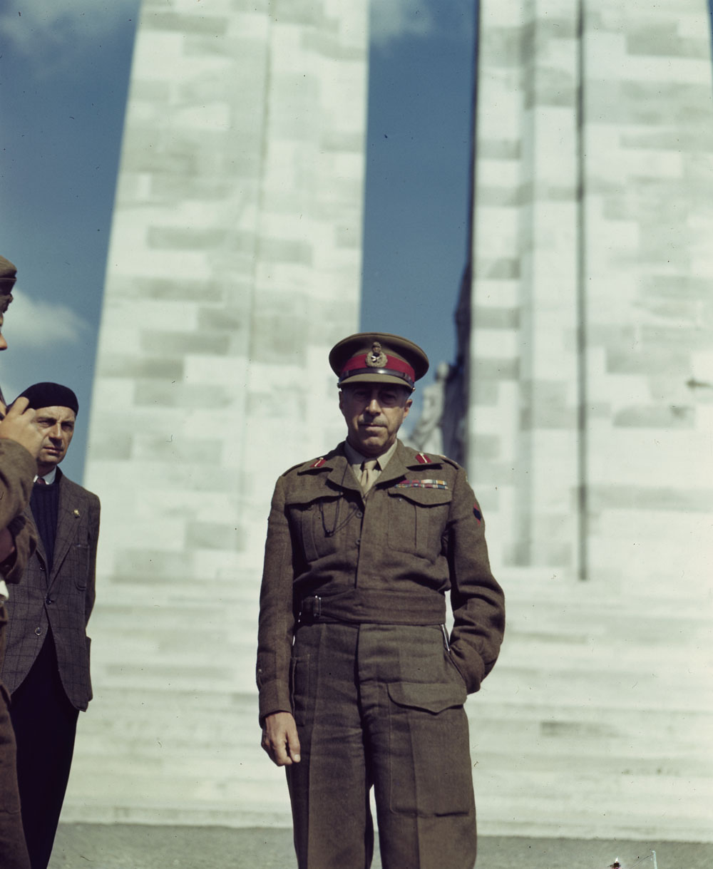 A colour photograph of a man in a military uniform standing in front of a stone war memorial. A man in a tweed coat and beret is partially visible nearby.
