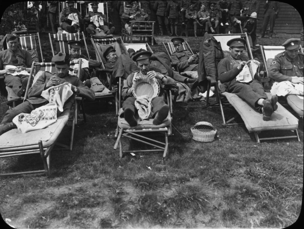 A black-and-white photograph of soldiers in uniform sitting outdoors while knitting.
