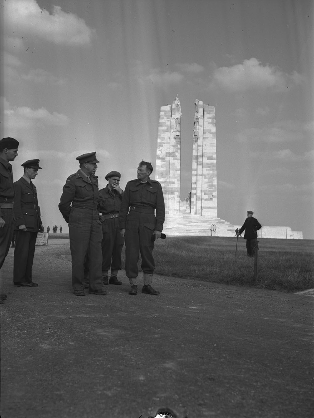 A group of men in military uniforms talking, watched from a distance by a man in civilian clothes. A stone war memorial featuring two tall vertical columns can be seen in the background.