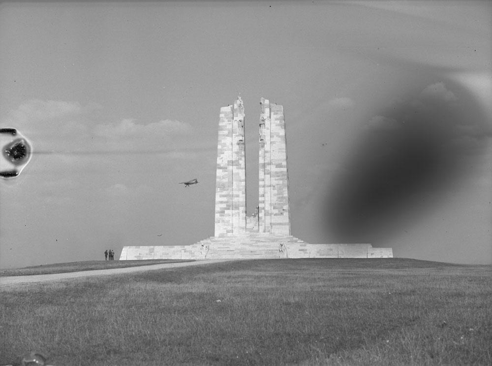 : A black-and-white photograph of a small airplane in the sky near a stone war memorial featuring two tall vertical columns.