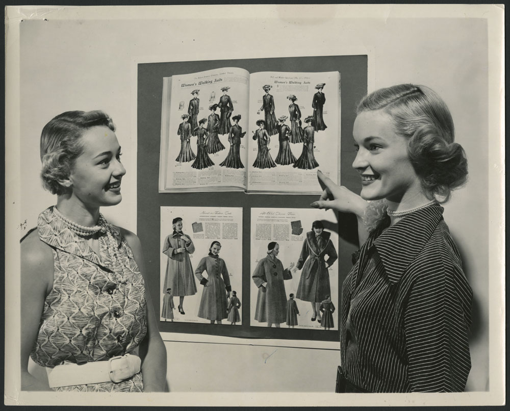 A black-and-white photograph showing two smiling women standing on each side of fashion catalogues from the late 19th century and mid-20th century.