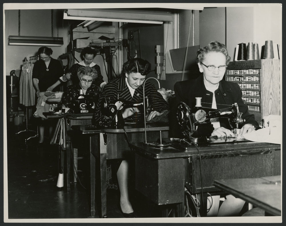 A black-and-white photograph showing two women ironing clothes and three women working at sewing machines.