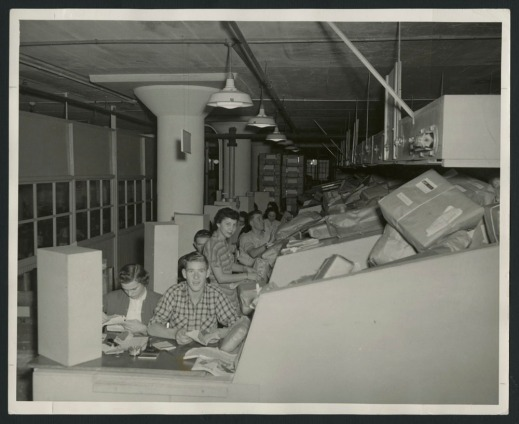 Two black-and-white photographs, one showing a group of employees sorting parcels into bins, and the other showing women at desks checking addresses on parcels as the parcels slide down a ramp toward them.
