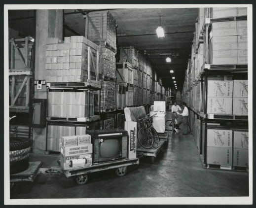 A black-and-white photograph showing two men checking paperwork in a large distribution centre, with merchandise visible on a series of rolling carts in the foreground and fluorescent lights overhead.