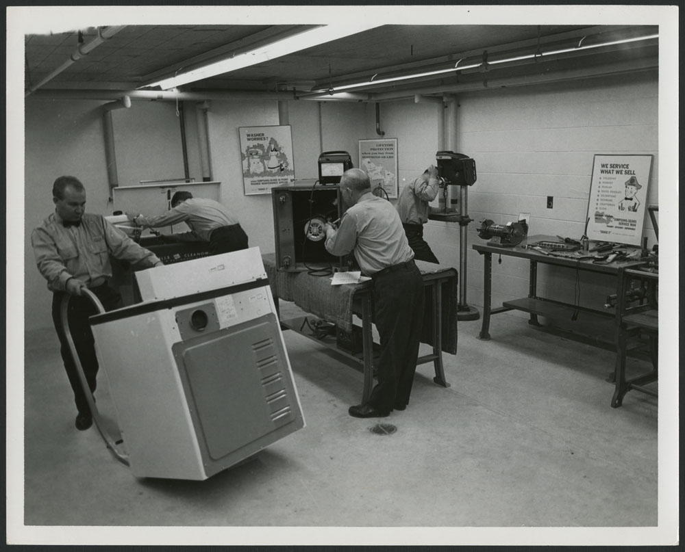 A black-and-white photograph showing three men repairing items in a workshop, and a fourth man moving a large appliance.