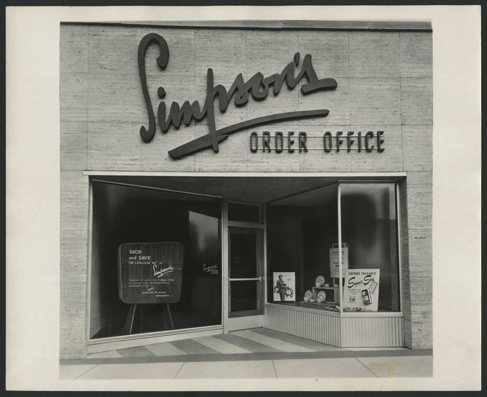 "A black-and-white photograph showing the exterior of a catalogue store, with ""Simpson's Order Office"" written above the door, and advertisements in the windows."