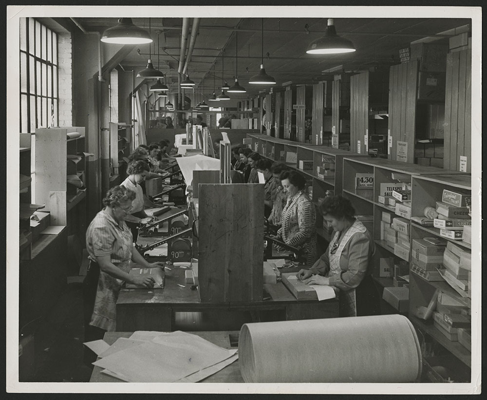 A black-and-white photograph showing two rows of women standing, wearing aprons and wrapping parcels at a long desk, with shelves containing parcels behind them, and a large roll of wrapping paper in the foreground.