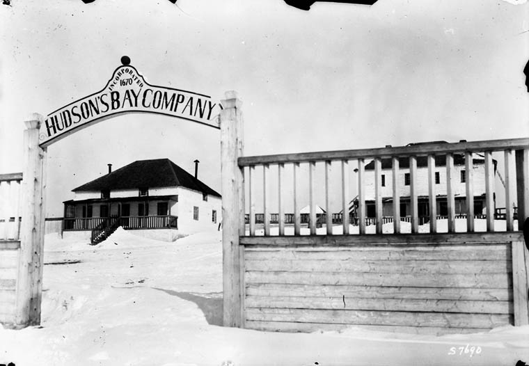"A black-and-white photograph of a building seen through a gate that reads ""Hudson's Bay Company, incorporated 1670"" and a second building seen beyond a fence to the right."