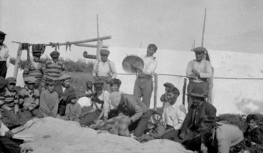 A black-and-white photograph of about 20 men and boys, some standing and some kneeling on the ground. One man near the centre of the photo is wearing a white buttoned-up shirt and dark pants with a wooden tobacco pipe in his mouth. He is hitting a caribou-skin hand drum with a wooden drumstick. There is a white canvas wall tent set up in the background, and fresh meat hanging to dry on a wooden rack.