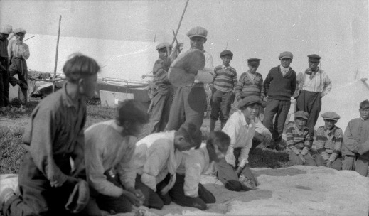 A black-and-white composite photograph of about 16 boys, some standing, some kneeling on the ground. They are playing Dene Handgame. One young man is standing and hitting a caribou-skin hand drum with a wooden drumstick.