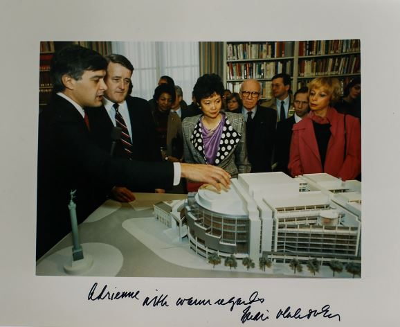 Several people looking at a model of a building.