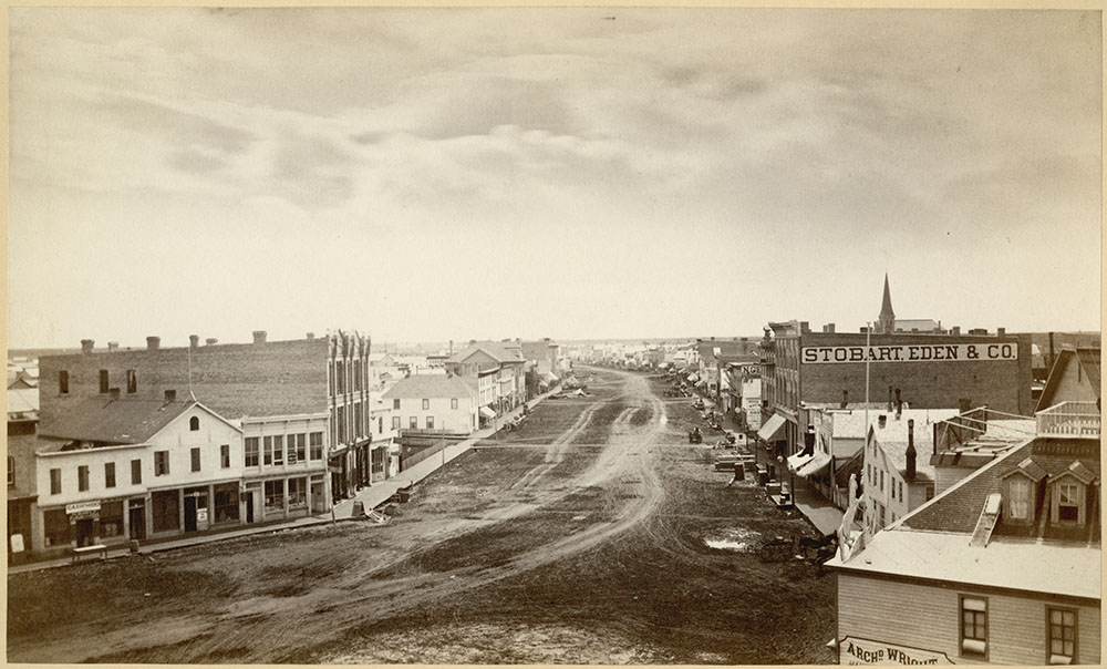 A sepia photograph of a town with buildings on either side of a wide dirt road with wagon tracks.
