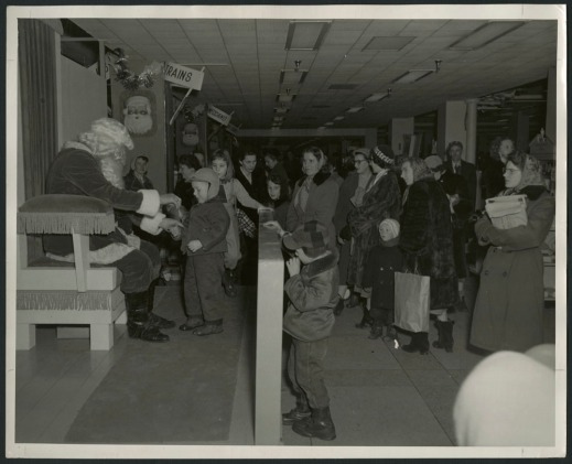 "Black-and-white photograph showing a little boy talking with Santa Claus, while other children and many parents, dressed for winter, are lined up nearby. In the background are two signs that read ""Trains"" and ""Meccano."""