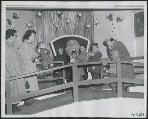 Black-and-white photograph showing children lined up to see Santa Claus, together with three adult women. Everyone is smiling, although some of the children look nervous.
