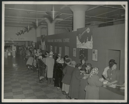 "Black-and-white photograph showing shoppers, mostly women, wearing winter coats and hats, studying catalogues at a counter, as well as the store staff behind the counter. There is a sign on the wall reading ""Catalogue Shopping Centre,"" together with Christmas decorations."
