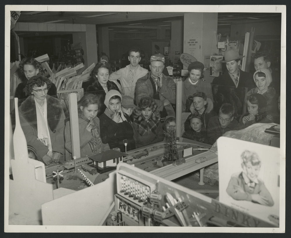 Black-and-white photograph showing a large group of men, women and children watching an electric train in a store.
