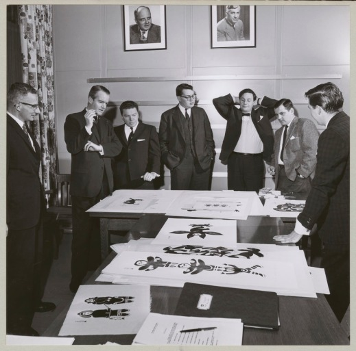 A black-and-white photograph of seven men in suits standing around a table and looking at art.