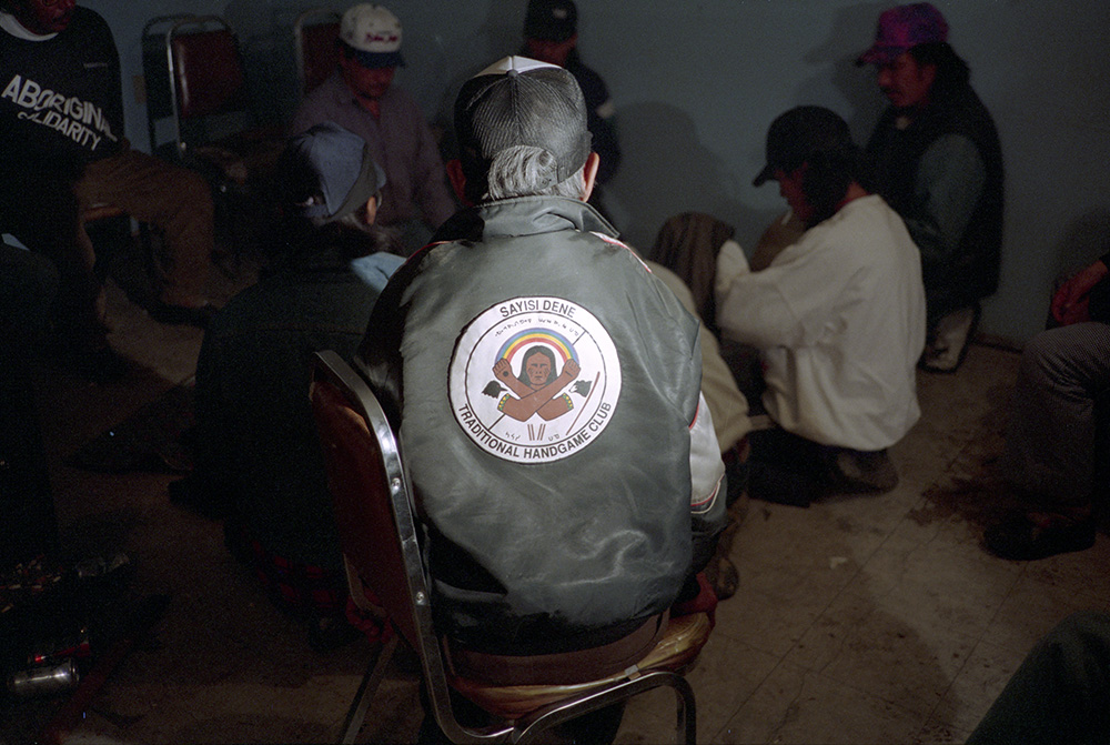 "A colour photograph of the back of an elderly man wearing a ""Sayisi Dene Traditional Handgame Club"" jacket, watching a Dene Handgame match."
