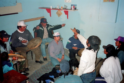 A colour photograph of eight men and one child. The men are playing Dene Handgame. Three of the men are hitting individual caribou-skin hand drums with wooden drumsticks. Two men are gesturing with Dene Handgame hand signals.